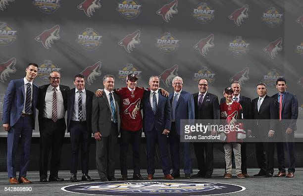 Clayton Keller poses onstage for a photo with the Arizona Coyotes team personnel after being selected seventh overall by the Arizona Coyotes during...