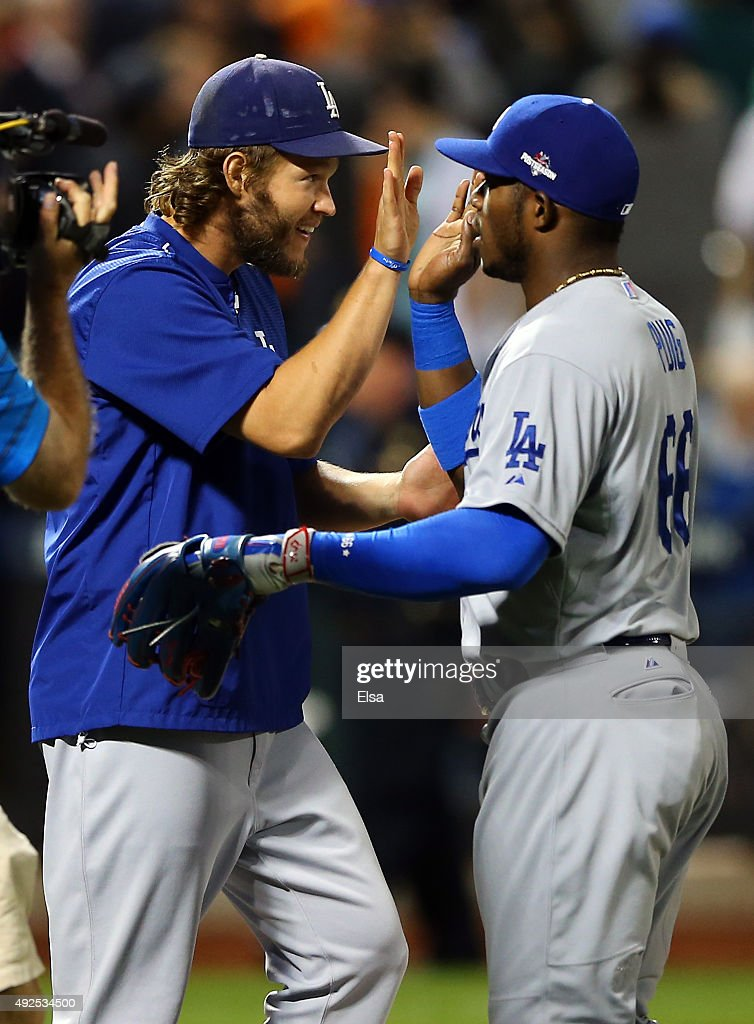 Clayton Kershaw #22 and Yasiel Puig #66 of the Los Angeles Dodgers celebrate after defeating the New York Mets in game four of the National League Division Series at Citi Field on October 13, 2015 in New York City. The Dodgers defeated the Mets with a score of 3 to 1.