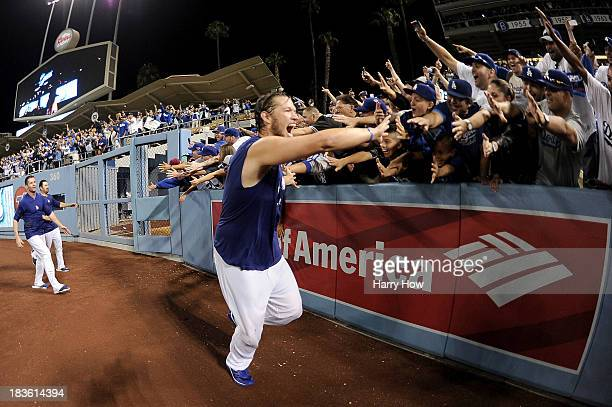 Clayton Kershaw of the Los Angeles Dodgers celebrates on the field with fans after the Dodgers defeat the Atlanta Braves 43 in Game Four of the...