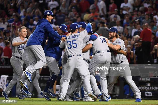 Clayton Kershaw of the Los Angeles Dodgers celebrates with Cody Bellinger and Yu Darvish after beating the Arizona Diamondbacks 31 to win the...