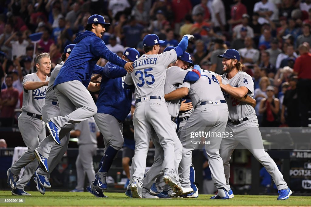 Clayton Kershaw #22 of the Los Angeles Dodgers (right) celebrates with Cody Bellinger #35 and Yu Darvish #21 (left) after beating the Arizona Diamondbacks 3-1 to win the National League Divisional Series at Chase Field on October 9, 2017 in Phoenix, Arizona.