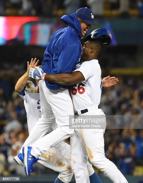 Clayton Kershaw of the Los Angeles Dodgers leaps into the arms of Yasiel Puig of the Los Angeles Dodgers after Puig hit a walk off threerun home run...