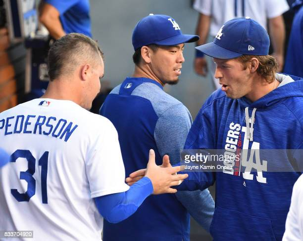 Clayton Kershaw of the Los Angeles Dodgers shakes hands with Joc Pederson in the dugout before the game against the Chicago White Sox at Dodger...