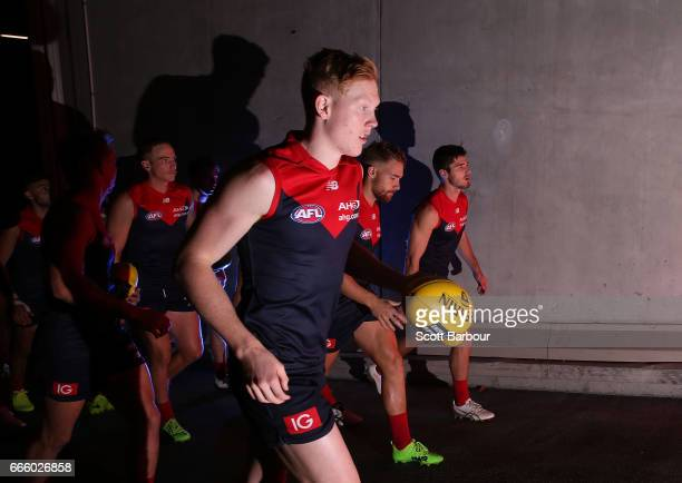 Clayton Oliver of the Demons and his teammates run onto the field during the round three AFL match between the Geelong Cats and the Melbourne Demons...