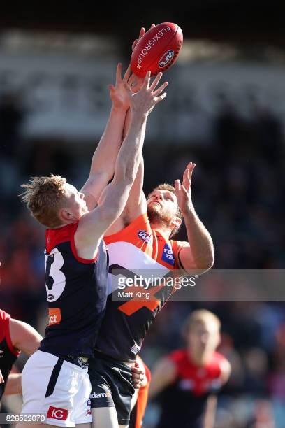 Clayton Oliver of the Demons competes for the ball against Shane Mumford of the Giants during the round 20 AFL match between the Greater Western...