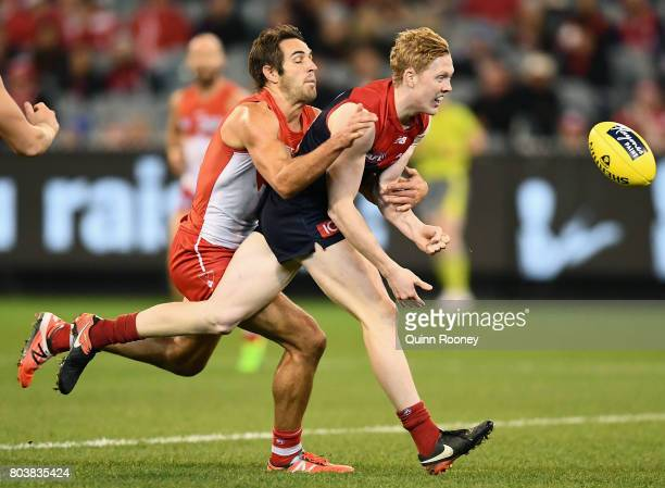 Clayton Oliver of the Demons handballs whilst being tackled by Josh Kennedy of the Swans during the round 15 AFL match between the Melbourne Demons...