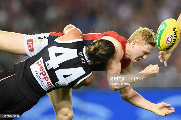 Clayton Oliver of the Demons handballs whilst being tackled by Maverick Weller of the Saints during the round one AFL match between the St Kilda...