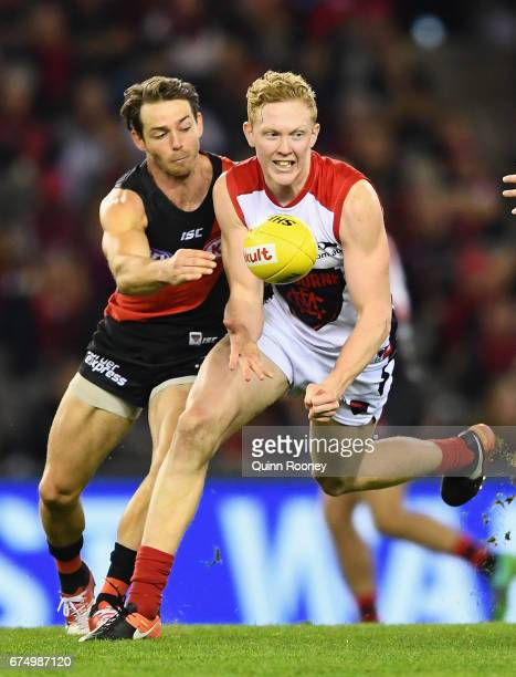 Clayton Oliver of the Demons handballs whilst being tackled by Travis Colyer of the Bombers during the round six AFL match between the Essendon...