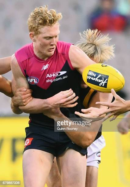 Clayton Oliver of the Demons handballs whilst being tackled Will Langford of the Hawks during the round seven AFL match between the Melbourne Demons...