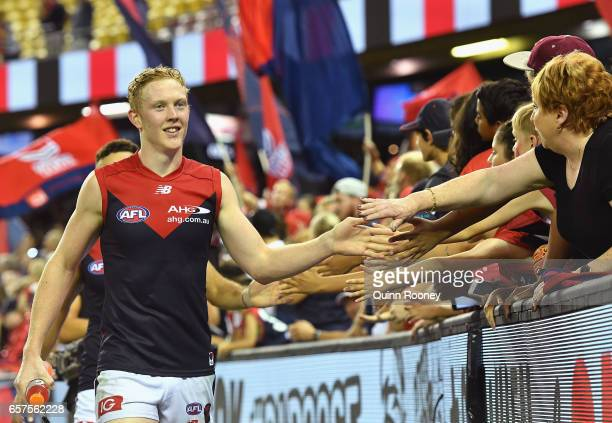 Clayton Oliver of the Demons high fives fans after winning the round one AFL match between the St Kilda Saints and the Melbourne Demons at Etihad...