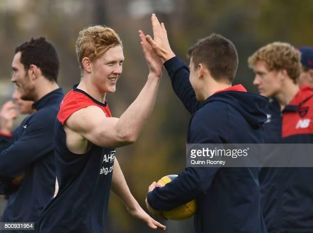 Clayton Oliver of the Demons high fives Jack Trengove during a Melbourne Demons AFL training session at Gosch's Paddock on June 26 2017 in Melbourne...