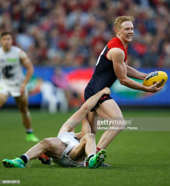 Clayton Oliver of the Demons is tackled by Bryce Gibbs of the Blues during the 2017 AFL round 02 match between the Melbourne Demons and the Carlton...