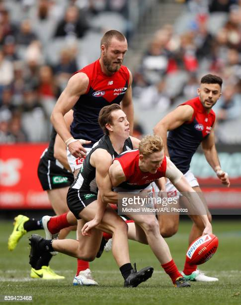 Clayton Oliver of the Demons is tackled by Callum Brown of the Magpies during the 2017 AFL round 23 match between the Collingwood Magpies and the...