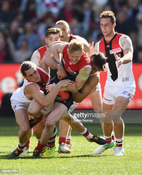 Clayton Oliver of the Demons is tackled by Jack Steele and Billy Longer of the Saints during the round 21 AFL match between the Melbourne Demons and...