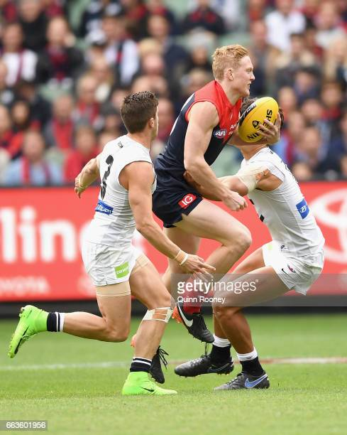 Clayton Oliver of the Demons is tackled by Marc Murphy and Jack Silvagni of the Blues during the round two AFL match between the Melbourne Demons and...