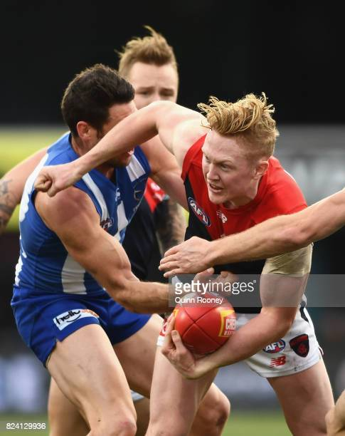 Clayton Oliver of the Demons is tackled by Sam Gibson of the Kangaroos during the round 19 AFL match between the North Melbourne Kangaroos and the...