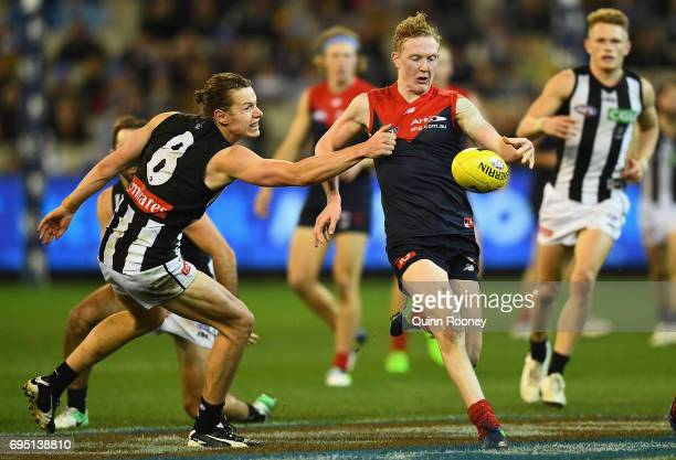 Clayton Oliver of the Demons kicks whilst being tackled by Tom Langdon of the Magpies during the round 12 AFL match between the Melbourne Demons and...