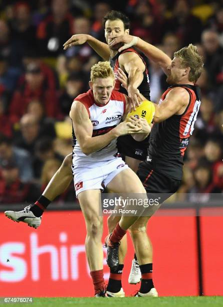 Clayton Oliver of the Demons marks infront of Matt Dea and Michael Hurley of the Bombers during the round six AFL match between the Essendon Bombers...