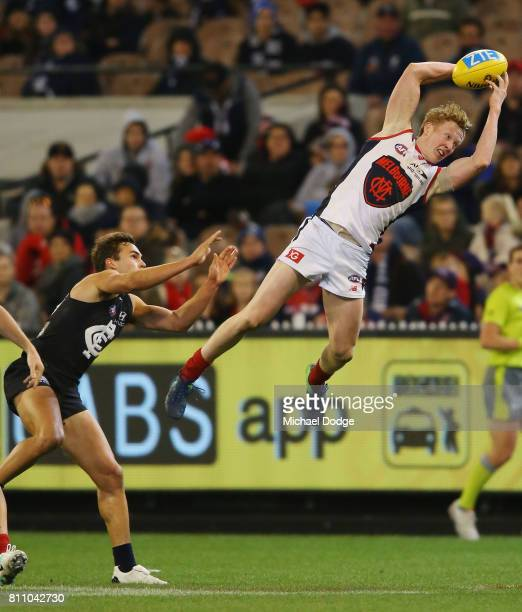 Clayton Oliver of the Demons marks the ball against David Cuningham of the Blues during the round 16 AFL match between the Carlton Blues and the...