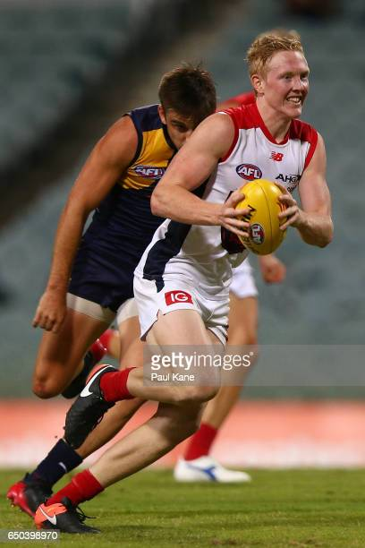 Clayton Oliver of the Demons runs with the ball during the JLT Community Series AFL match between the West Coast Eagles and the Melbourne Demons at...