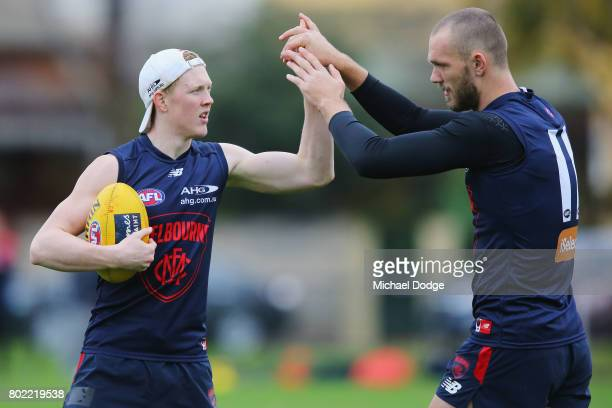 Clayton Oliver slaps hands with Max Gawn during a Melbourne Demons AFL training session at Gosch's Paddock on June 28 2017 in Melbourne Australia