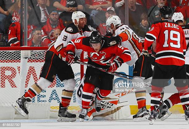 Clayton Stoner and Josh Manson of the Anaheim Ducks combine to hit Taylor Hall of the New Jersey Devils during the third period at the Prudential...