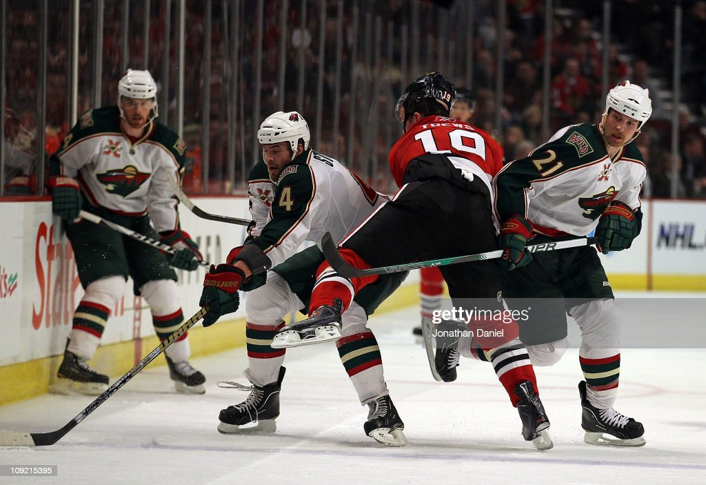 Clayton Stoner and Kyle Brodziak of the Minnesota Wild squeeze out Jonathan Toews of the Chicago Blackhawks as Stoner tries to control the puck at...
