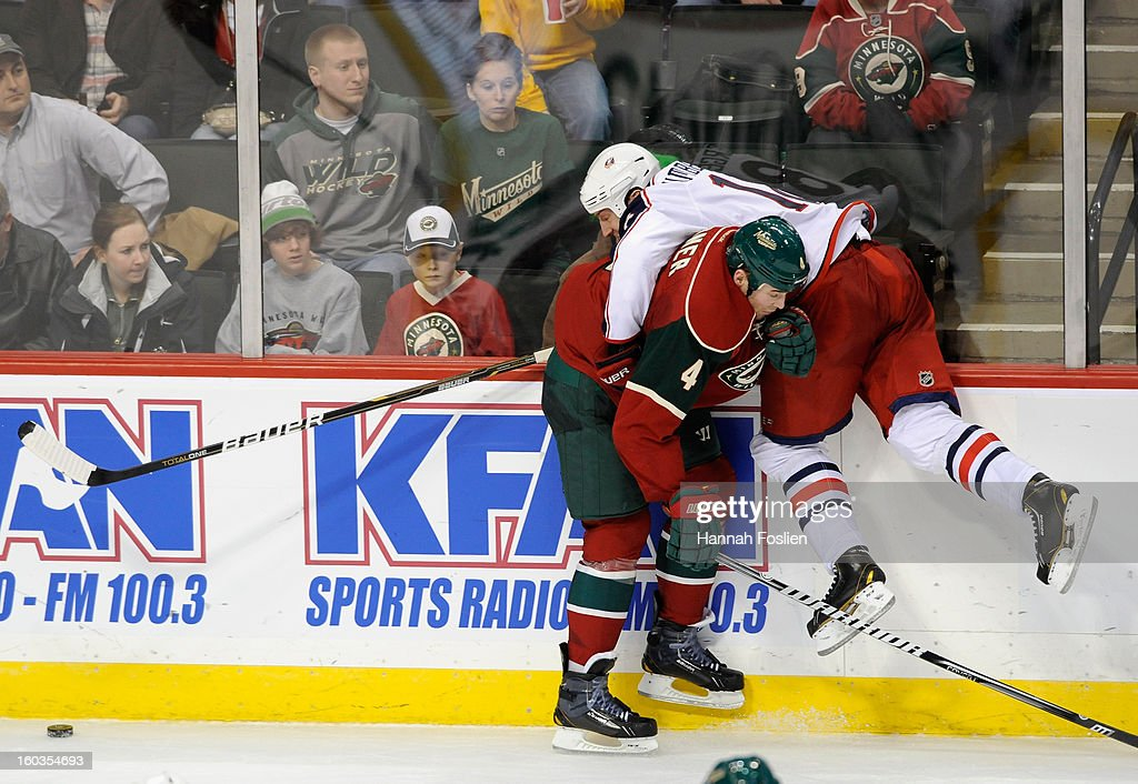<a gi-track='captionPersonalityLinkClicked' href=/galleries/search?phrase=Clayton+Stoner&family=editorial&specificpeople=2222214 ng-click='$event.stopPropagation()'>Clayton Stoner</a> #4 of the Minnesota Wild checks <a gi-track='captionPersonalityLinkClicked' href=/galleries/search?phrase=R.J.+Umberger&family=editorial&specificpeople=636608 ng-click='$event.stopPropagation()'>R.J. Umberger</a> #18 of the Columbus Blue Jackets into the boards during the third period of the game on January 29, 2013 at Xcel Energy Center in St Paul, Minnesota. The Wild defeated the Blue Jackets 3-2.