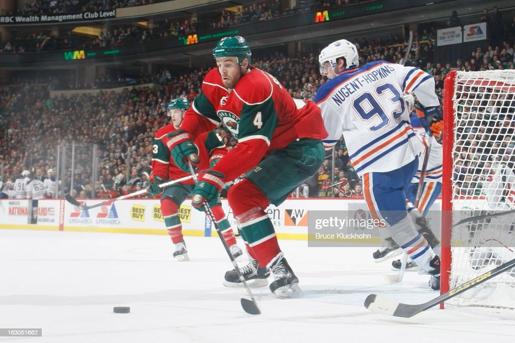<a gi-track='captionPersonalityLinkClicked' href=/galleries/search?phrase=Clayton+Stoner&family=editorial&specificpeople=2222214 ng-click='$event.stopPropagation()'>Clayton Stoner</a> #4 of the Minnesota Wild handles the puck near his own goal with <a gi-track='captionPersonalityLinkClicked' href=/galleries/search?phrase=Ryan+Nugent-Hopkins&family=editorial&specificpeople=7144190 ng-click='$event.stopPropagation()'>Ryan Nugent-Hopkins</a> #93 of the Edmonton Oilers defending during the game on March 3, 2013 at the Xcel Energy Center in Saint Paul, Minnesota.