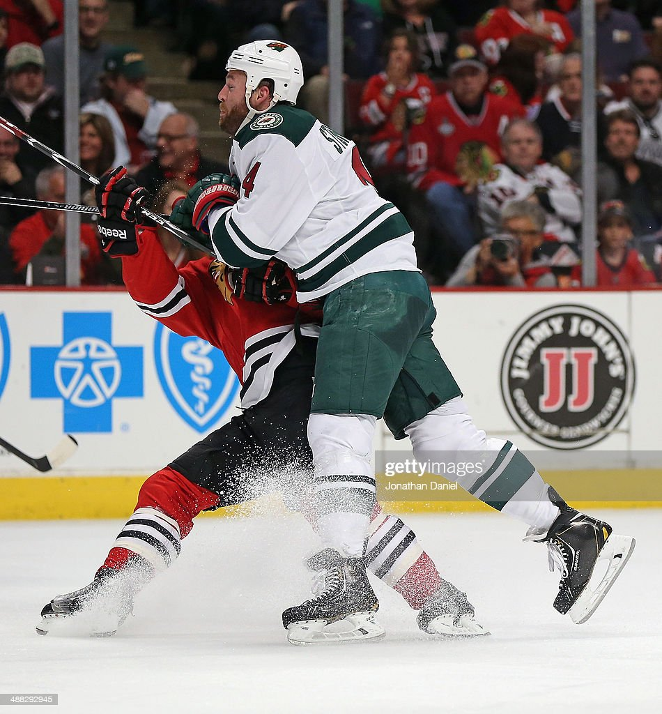 Clayton Stoner #4 of the Minnesota Wild knocks down Ben Smith #28 of the Chicago Blackhawks in Game Two of the Second Round of the 2014 NHL Stanley Cup Playoffs at the United Center on May 4, 2014 in Chicago, Illinois. The Blackhawks defeated the Wild 4-1.