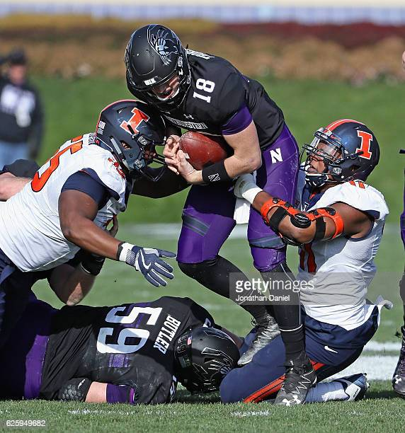 Clayton Thorson of the Northwestern Wildcats is sacked by Jamal Milan and Jimmy Marchese of the Illinois Fighting Illini at Ryan Field on November 26...