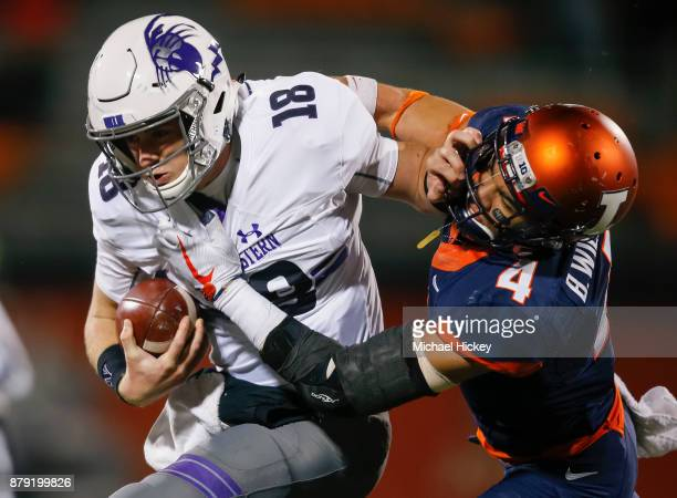 Clayton Thorson of the Northwestern Wildcats runs the ball as Bennett Williams of the Illinois Fighting Illini tries to make the tackle at Memorial...