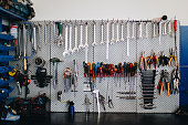 Wrenches and other tools hanging on the wall in workshop, front view