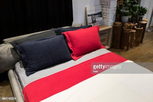 A Clean Bedroom with White Bed Sheet, Single Bed,  Red and Black Pillow