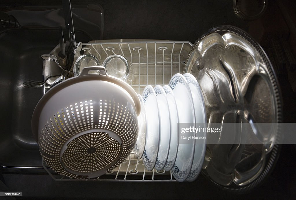 Kitchen Sink With Clean Dishes clean dishes in kitchen sink dish rack overhead view stock photo