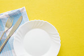 Clean, empty, white plate, fork and knife with yellow tablecloth and blue towel on a table. Cutlery concept. Flat lay. Top view. Free space for text or a logo.