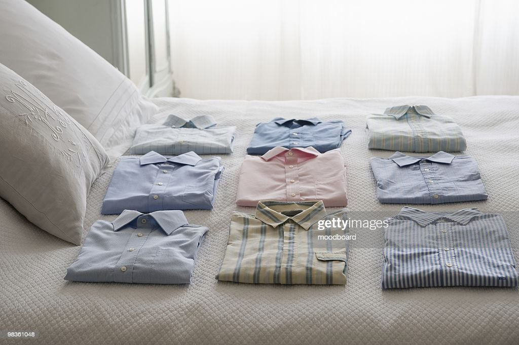 Clean shirts ordered on a bed : Stock Photo