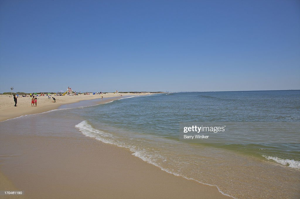 Clean smooth shoreline, people in distance. : Stock Photo