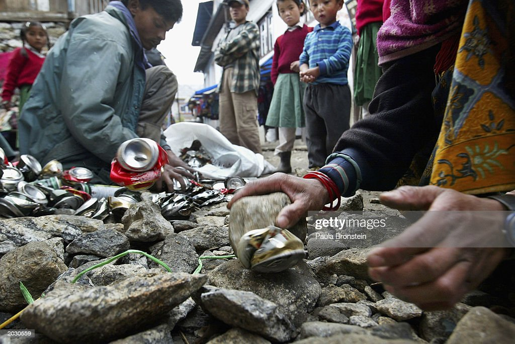 A clean up campaign continues on the Everest trail in Lukla May, 25 2003 in the Solu Khumbu region, Nepal. Tin cans are smashed with rocks so that they can be carried out easily and bottles are no longer encouraged in order to limit the amount and the weight of the garbage that collects from all the trekkers. A record 1,000 climbers plan an assault on the summit as mountaineers celebrate the 50-year anniversary of the conquest of Everest. The Golden Jubilee marks the conquest of Sir Edmund Hillary and Sherpa Tenzing Norgay who were the first to scale the world's highest mountain, reaching the summit on May 29th, 1953.