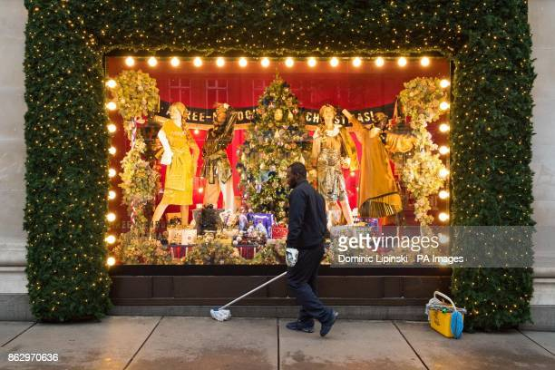A cleaner at work outside a Christmas window display themed as With Love From which is a celebration of the cities Selfridges calls home at Sefridges...