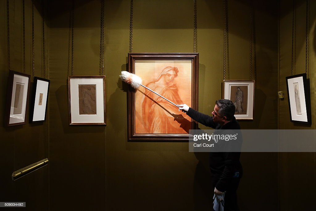 A cleaner dusts a painting by George Frederic Watts entitled 'Study of the Figure of Death for Time, Death and Judgement' during a preview at Leighton House Museum on February 10, 2016 in London, England. The worst form part of the Pre-Raphaelites on Paper exhibition, which will run from 12th February to 29th May 2016.
