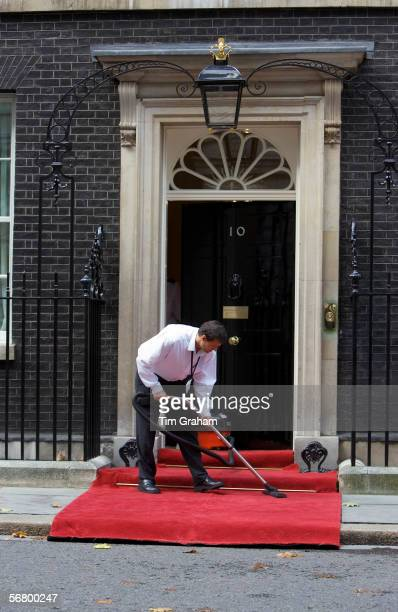 Cleaner hoovers the carpet outside Number 10 Downing Street the home of the British Prime Minister London United Kingdom