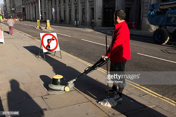Cleaner in the city on a quiet weekend manoeuvres his floor polishing machine across the pavement It looks weird as if he's cleaning the street...