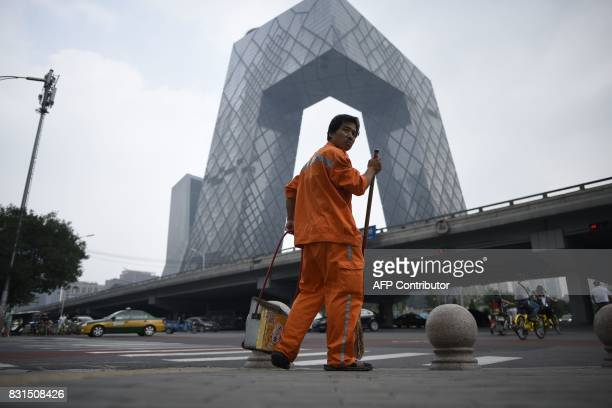 A cleaner looks on as the CCTV Tower looms in the background in the central business district in Beijing on August 15 2017 The International Monetary...