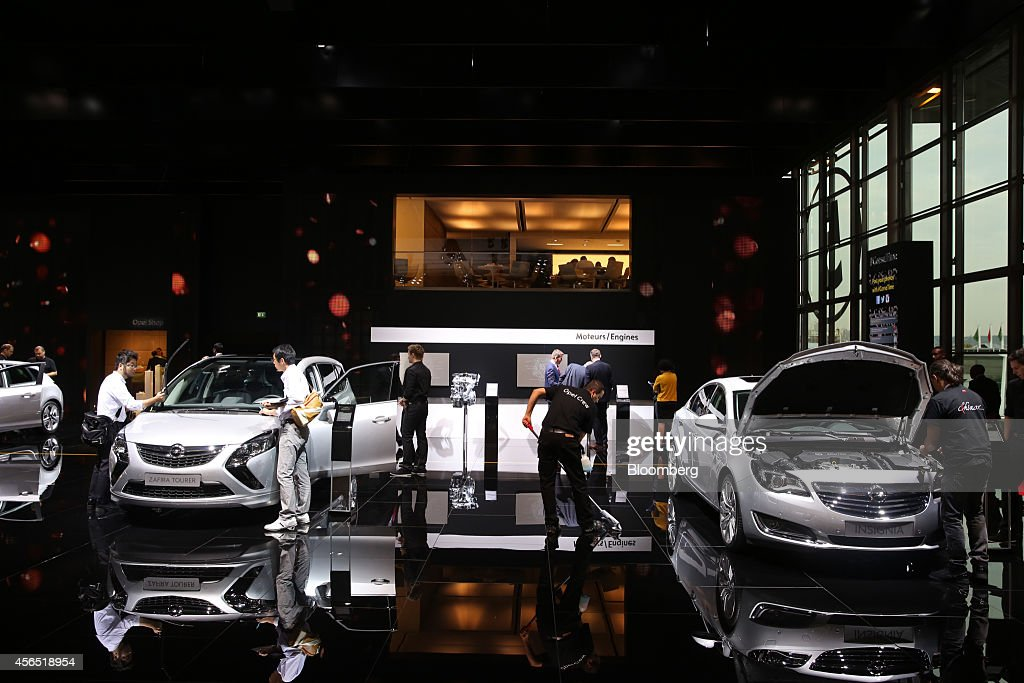 A cleaner polishes the floor between an Opel Zafira Tourer left and an Opel Insignia automobile at the Adam Opel AG stand on the first preview day at...