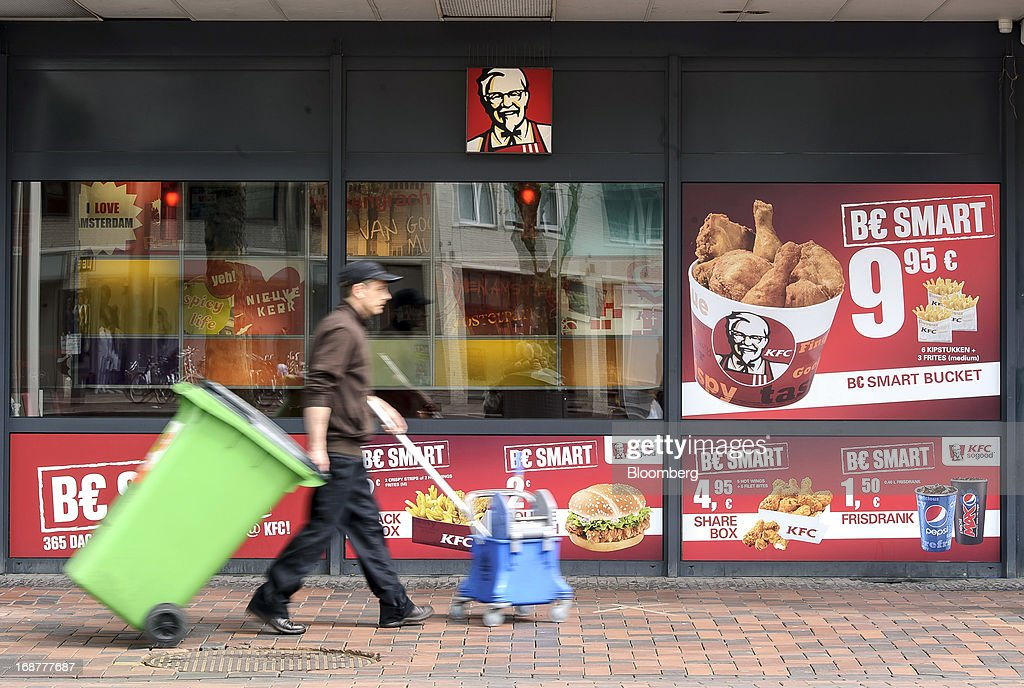 A cleaner, pulling a green wheelie bin, walks past a KFC fast-food restaurant, owned by Yum! Brands Inc. in the Dutch city of Amsterdam, Netherlands, on Tuesday, May 14, 2013. Euro-area data this week will probably reveal economic scars of the sovereign debt crisis confirming that the region is now suffering the longest recession since the single currency's creation. Photographer: Jock Fistick/Bloomberg via Getty Images