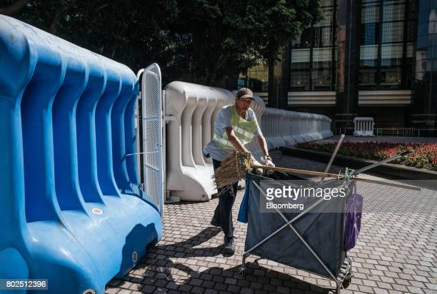 A cleaner pushes a cart past water barricades near the Hong Kong Convention and Exhibition Center ahead of Chinese President Xi Jinping's arrival in...