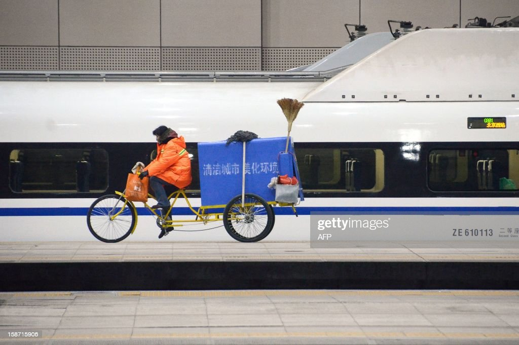 A cleaner rides a tricycle past a high-speed train running from the Beijing to Guangzhou, south China's Guangdong province, at the Beijing west railway station in Beijing on December 26, 2012. China on December 26 started service on the world's longest high-speed rail route, the latest milestone in the country's rapid and sometimes troubled super fast rail network. AFP PHOTO / WANG ZHAO
