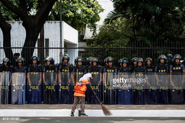 TOPSHOT A cleaner sweeps in front of police standing in formation near the venue of the Association of Southeast Asian Nations summit off Manila Bay...