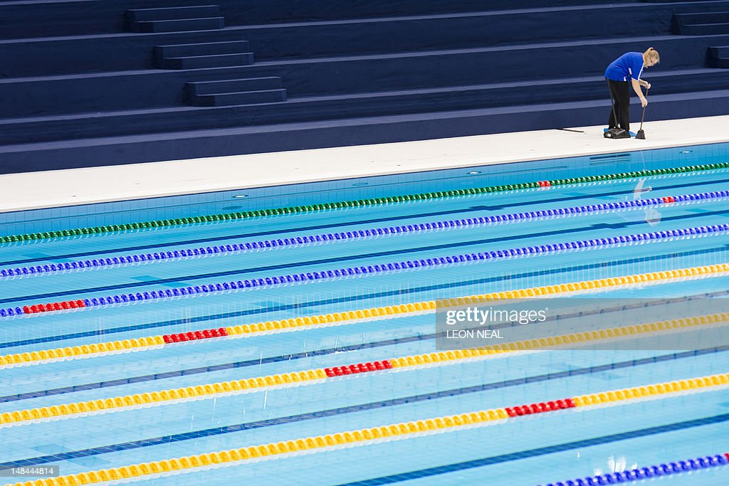 a cleaner sweeps the deck beside the swimming pool at the aquatics centre in the olympic